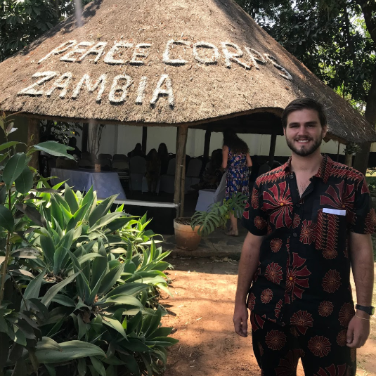 Nick Nagy in front of Peace Corps Zambia sign